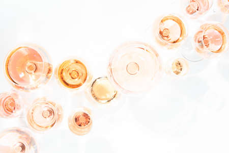 Many glasses of rose wine at wine tasting. Concept of rose wine and variety. White background. Top view, flat lay design. Toned  overlight image. Horizontal Stock Photo