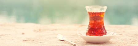 Hot turkish tea outdoors near water. Turkish tea and traditional turkish culture concept. Horizontal, banner format. Toned image, warm sunset light