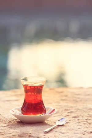Hot turkish tea outdoors near water. Turkish tea and traditional turkish culture concept. Vertical. Toned image, warm sunset light