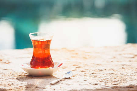 Hot turkish tea outdoors near water. Turkish tea and traditional turkish culture concept. Horizontal. Toned image