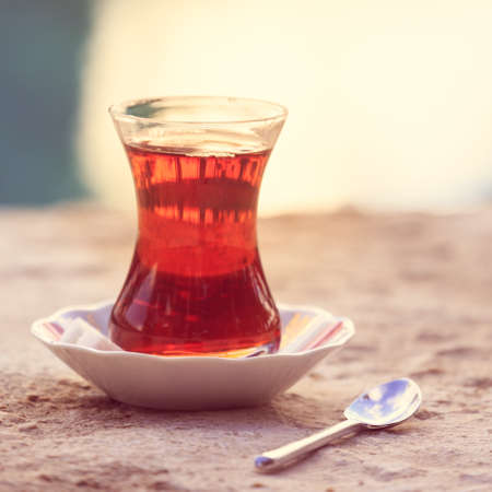Hot turkish tea outdoors near water. Turkish tea and traditional turkish culture concept. Square. Toned image, warm sunset light