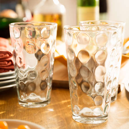 Concept of friendly family dinner party preparation. Warm light, shallow depth of field. Square