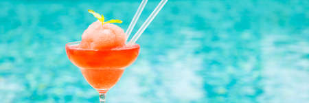 Frozen strawberry margarita cocktail at the edge of a resort pool. Concept of luxury vacation. Outdoor pool background. Horizontal, wide screen banner format Stock Photo