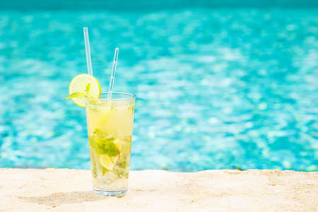 Mojito cocktail at the edge of a resort pool. Concept of luxury vacation. Outdoor pool background. Horizontal