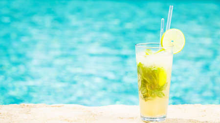 Mojito cocktail at the edge of a resort pool. Concept of luxury vacation. Outdoor pool background. Horizontal, wide screen format