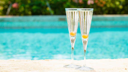 Two glasses of prosecco cocktail with orange berry at the edge of a resort pool. Concept of luxury vacation. Outdoor pool background. Horizontal, wide screen format