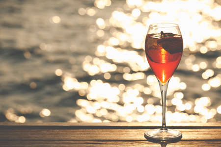 Aperol spritz at a wooden pier at sunset. Luxury resort vacation concept. Festive relax getaway background. Horizontal, toned image