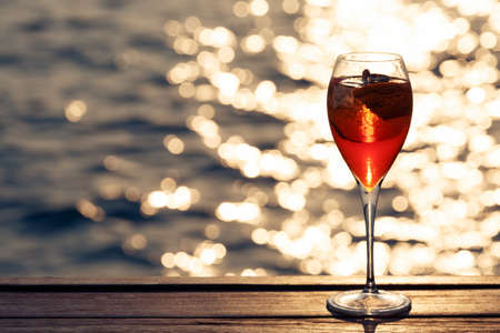 spritz: Aperol spritz at a wooden pier at sunset. Luxury resort vacation concept. Festive relax getaway background. Horizontal, toned image