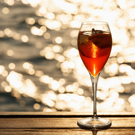 spritz: Aperol spritz at a wooden pier at sunset. Luxury resort vacation concept. Festive relax getaway background. Square, toned image