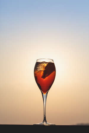 Aperol spritz at a wooden pier at sunset. Luxury resort vacation concept. Festive relax getaway background. Toned image. Vertical Stock Photo