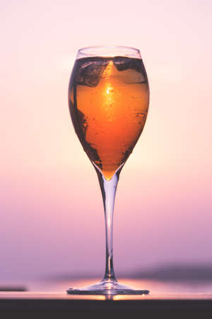 spritz: Aperol spritz at a wooden pier at sunset. Luxury resort vacation concept. Festive relax getaway background. Toned image. Vertical Stock Photo