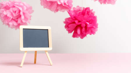 expected: Empty small charcoal board at the girl baby shower party. Baby shower celebration concept. Festive party background. Horizontal, wide screen format