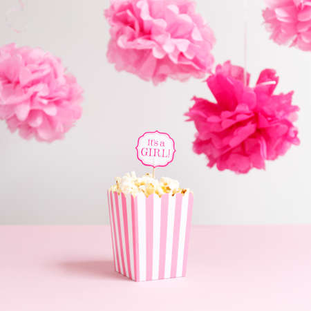 corn flower: Its a girl sign in a popcorn bag at the baby shower party. Baby shower celebration concept. Festive party background. Square Stock Photo