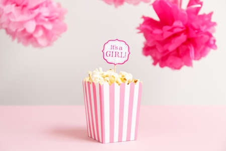 Its a girl sign in a popcorn bag at the baby shower party. Baby shower celebration concept. Festive party background. Horizontal