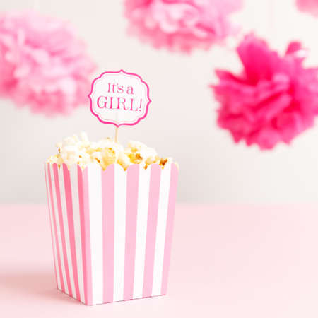 Its a girl sign in a popcorn bag at the baby shower party. Baby shower celebration concept. Festive party background. Square Stock Photo