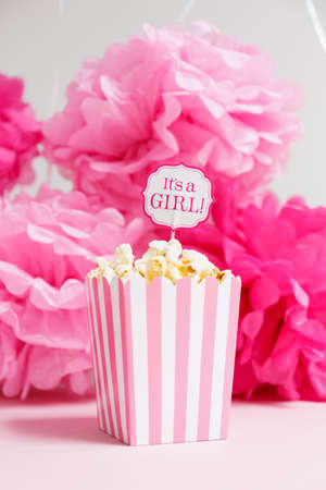 corn flower: Its a girl sign in a popcorn bag at the baby shower party.  Paper flowers background. Baby shower celebration concept. Festive party background. Vertical