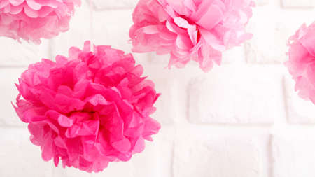 Paper flowers at the girl baby shower party. Baby shower celebration concept. Festive party background. Horizontal, wide screen format, white brick background Stock Photo