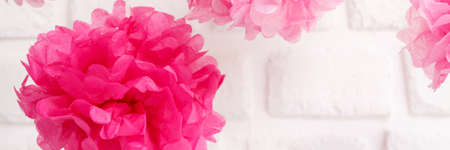 Paper flowers at the girl baby shower party. Baby shower celebration concept. Festive party background. Horizontal, wide screen format, banner format, white brick background