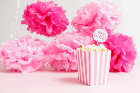 Its a girl sign in a popcorn bag at the baby shower party.  Paper flowers background. Baby shower celebration concept. Festive party background. Horizontal Stock Photo
