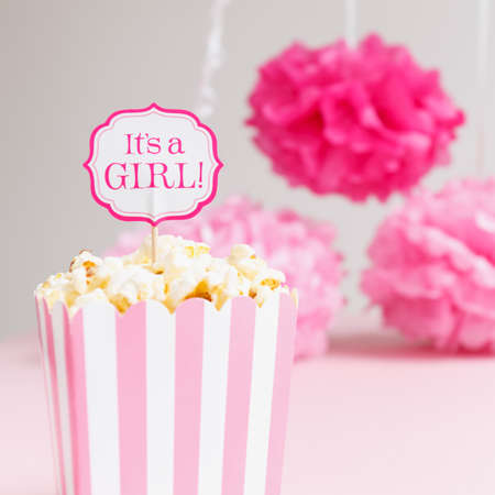 Its a girl sign in a popcorn bag at the baby shower party.  Paper flowers background. Baby shower celebration concept. Festive party background. Square