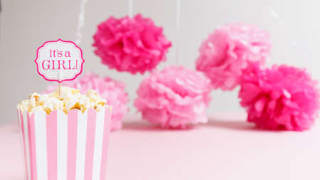 Its a girl sign in a popcorn bag at the baby shower party.  Paper flowers background. Baby shower celebration concept. Festive party background. Horizontal, wide screen format 版權商用圖片