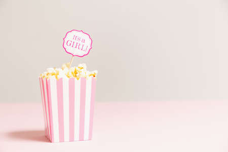 Its a girl sign in a popcorn bag at the baby shower party.  Empty background. Baby shower celebration concept. Festive party background. Horizontal Stock Photo