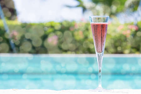 Glass of Kir Royal cocktail on the pool nosing at the tropical resort. Horizontal, cocktail on right side. Bokeh details