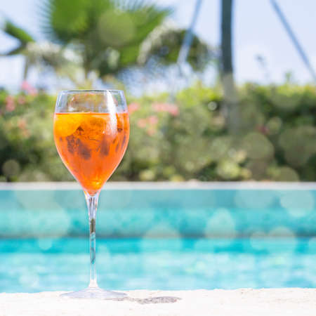 spritz: Glass of Aperol Spritz cocktail on the pool nosing at the tropical resort. Square, cocktail on left side. Bokeh details Stock Photo