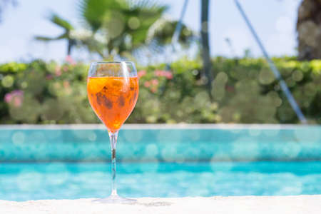 Glass of Aperol Spritz cocktail on the pool nosing at the tropical resort. Horizontal, cocktail on left side. Bokeh details