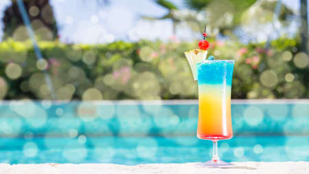 Glass of Rainbow cocktail on the pool nosing at the tropical resort. Horizontal, wide screen, cocktail on right side. Bokeh details