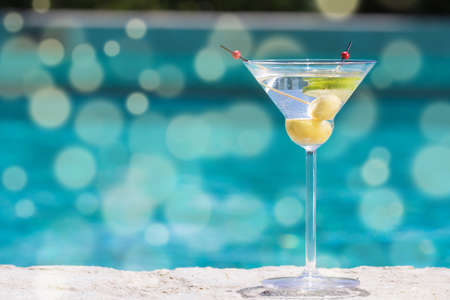Glass of dry martini cocktail on the pool nosing at the tropical resort. Horizontal. Bokeh details Standard-Bild