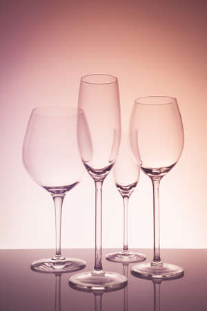 Glassware selection with wine, champagne and liquour glasses on creative background.. Fine cristal glassware concept. Vertical, warm tone Stock Photo