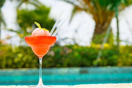 edge: Frozen strawberry margarita cocktail at the edge of a resort pool. Concept of luxury vacation. Outdoor pool background. Horizontal Stock Photo
