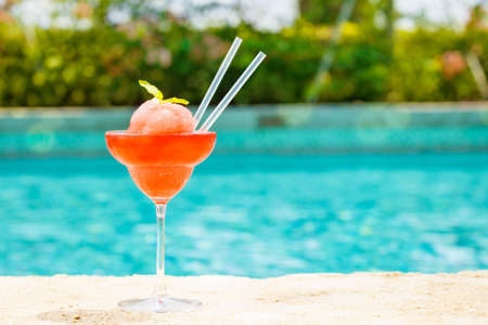 Frozen strawberry margarita cocktail at the edge of a resort pool. Concept of luxury vacation. Outdoor pool background. Horizontal Stock Photo