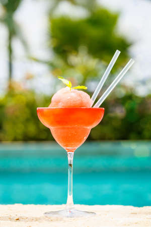 edge: Frozen strawberry margarita cocktail at the edge of a resort pool. Concept of luxury vacation. Outdoor pool background. Vertical