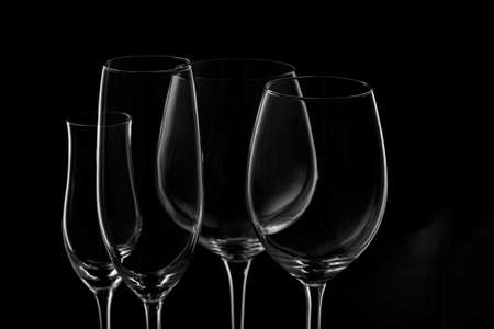 in low spirits: Glassware selection with wine, champagne and liquour glasses on the dark background.. Fine cristal glassware concept. Horizontal Stock Photo