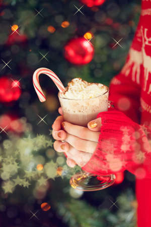 Girl holding cacao with whipped cream and peppermint candy cane. Christmas holiday concept. Holiday background. Holiday or winter background. Vertical Vertical,  with fantasy stars bokeh