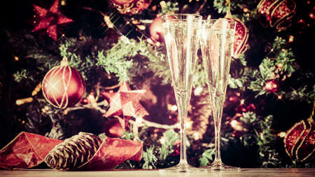 Two glasses of champagne with Christmas tree background. Holiday season background. Traditional red and green Christmas decoration with lights. Holiday party. Horizontal, wide screen format, with sparkles and toned