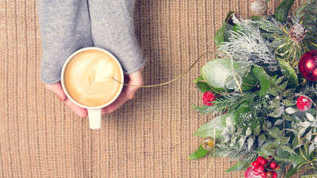 Girl holding cup of coffee with latte art. Christmas background. Hygge and leisure time concept. Pastel colors, warm toning. Horizontal, wide screen format