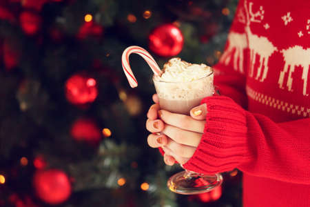 Girl holding cacao with whipped cream and peppermint candy cane. Christmas holiday concept. Holiday background. Holiday or winter background. Horizontal