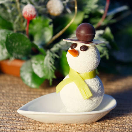 Snowman cake with Christmas decorations. Kids funny desserts concept. Christmas background. Square