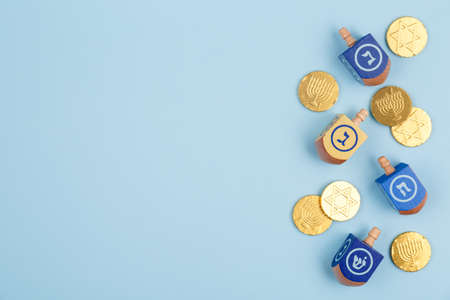 Blue background with multicolor dreidels and chocolate coins. Hanukkah and judaic holiday concept. Horizontal Stock Photo