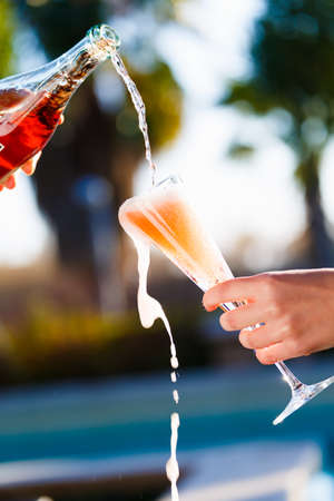 Waiter is pourring sparkling wine into a woman glass at the outdoor party.  Celebration concept. Event, party, wedding background. Toned image. Vertical