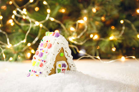Gingerbread house with Christmas tree background. Holiday concept. Horizontal