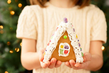 Girl holding a gingerbread house with Christmas tree background. Holiday concept. Horizontal