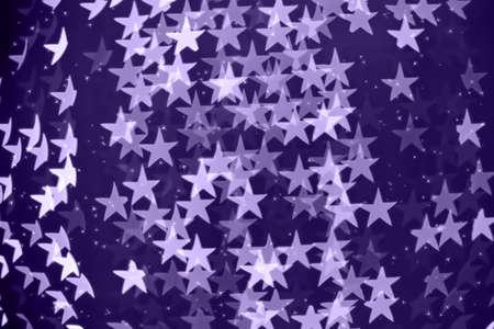星の形をした休日には、背景のボケ味がぼやけています。キラキラとクリスマスの背景。お祝いの背景。水平.ウルトラ バイオレット トーン、2018 年
