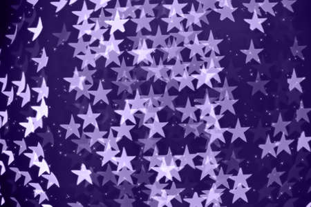 Star shaped holiday blurred bokeh background. Christmas background with sparkles. Celebration background. Horizontal.. Ultra violet tone, color of the year 2018