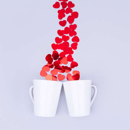 White china mug with  glitter heart confetti. Valentine day concept. Trendy minimalistic flat lay design background. Square