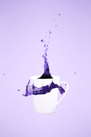 Levitating coffee mug with splashes. Coffee concept. Minimal art trend. Solid background. Vertical, straight cup, ultra violet tone, color of the year