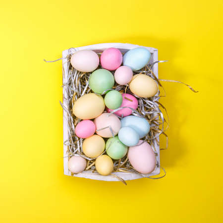 Multicolor eggs in a white tray. Creative Easter concept. Modern solid yellow background. Square Stock Photo